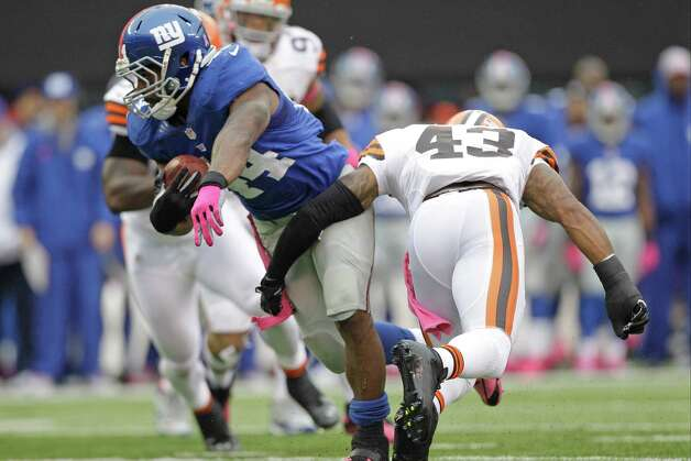 New York Giants running back Ahmad Bradshaw (44) breaks a tackle by Cleveland Browns strong safety T.J. Ward (43) during the first half of an NFL football game Sunday, Oct. 7, 2012, in East Rutherford, N.J. (AP Photo/Kathy Willens) Photo: Kathy Willens / AP