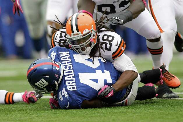 New York Giants running back Ahmad Bradshaw (44) is tackled by Cleveland Browns free safety Usama Young (28) during the first half of an NFL football game Sunday, Oct. 7, 2012, in East Rutherford, N.J. (AP Photo/Kathy Willens) Photo: Kathy Willens / AP