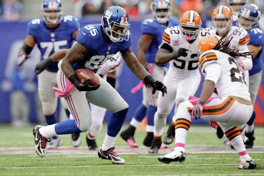 New York Giants tight end Martellus Bennett (85) runs away from Cleveland Browns free safety Usama Young (28) during the first half of an NFL football game Sunday, Oct. 7, 2012, in East Rutherford, N.J. (AP Photo/Kathy Willens) Photo: Kathy Willens / AP