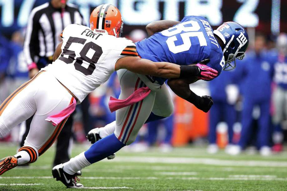 New York Giants tight end Martellus Bennett (85) breaks a tackle by Cleveland Browns linebacker Marcus Benard (58) during the first half of an NFL football game Sunday, Oct. 7, 2012, in East Rutherford, N.J. (AP Photo/Kathy Willens) Photo: Kathy Willens / AP