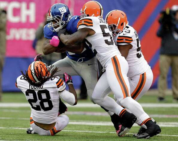 New York Giants running back Ahmad Bradshaw (44) is tackled by Cleveland Browns middle linebacker D'Qwell Jackson (52),  Craig Robertson (53) and  Usama Young (28) during the first half of an NFL football game Sunday, Oct. 7, 2012, in East Rutherford, N.J. (AP Photo/Kathy Willens) Photo: Kathy Willens / AP