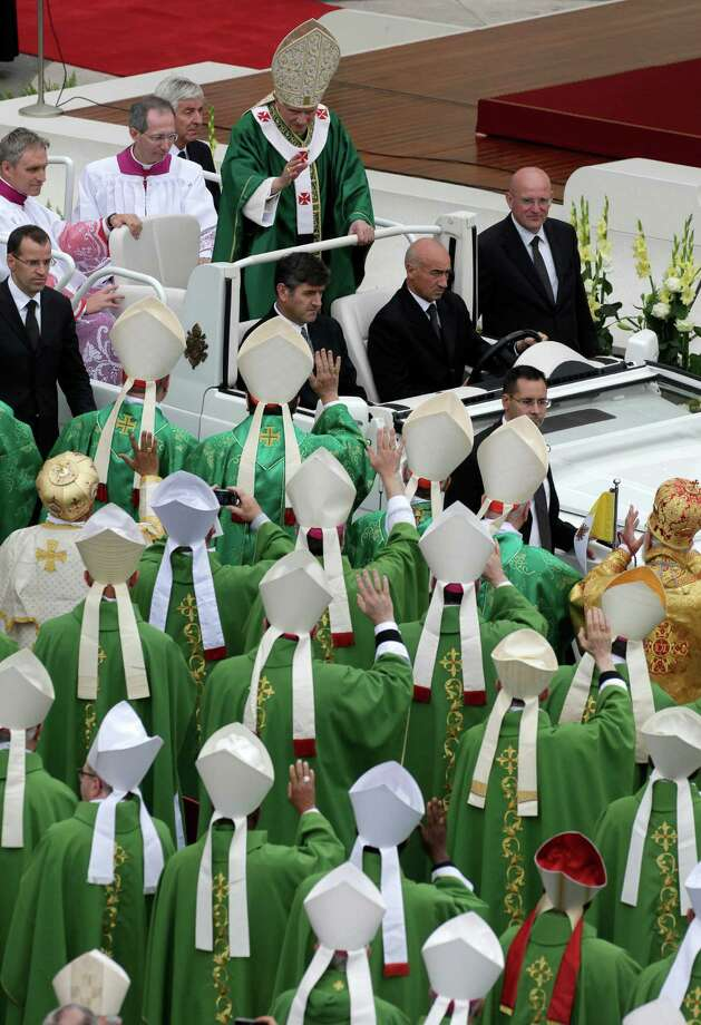 "Pope Benedict XVI, top, waves from his car to bishops at the end of a mass he celebrated for the opening of the synod of bishops in St. Peter's Square, at the Vatican, Sunday, Oct. 7, 2012. Pope Benedict XVI has also named two new ""doctors"" of the church, conferring the Catholic Church's highest honor on a 16th-century Spanish preacher St. John of Avila, and  to St. Hildegard of Bingen, and a 12th century German mystic who wasn't officially recognized as a saint until earlier this year. Photo: Alessandra Tarantino, Associated Press / AP"