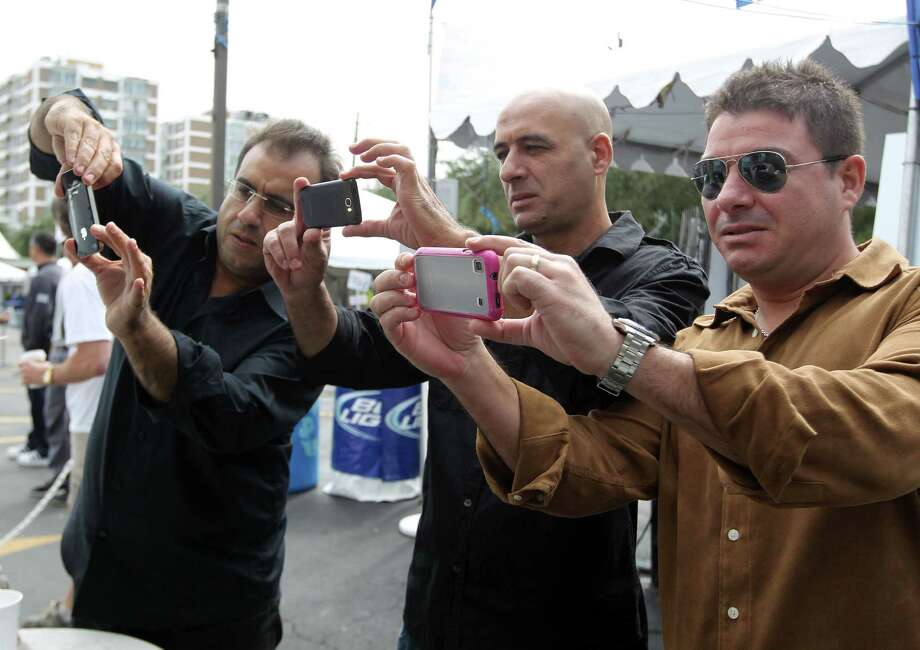 Raymond Nehma left, and Michael Smaha center and Dimitri Chalawit right take a photograph withh the cellular phones of the Souvlaki grill during The Original Greek Festival at the Annunciation Orthodox Cathedral Sunday, Oct. 7, 2012, in Houston. The festival prepared 21,168 Souvlaki tenderloin and onion kabobs for the four day festival. Photo: James Nielsen, Chronicle / © Houston Chronicle 2012