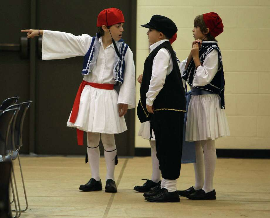 Richard Jacky left, Andrew Lambaakis center, and Stephano Cotsoradis talk before a children's dance program performance during The Original Greek Festival at the Annunciation Orthodox Cathedral Sunday, Oct. 7, 2012, in Houston. Photo: James Nielsen, Chronicle / © Houston Chronicle 2012
