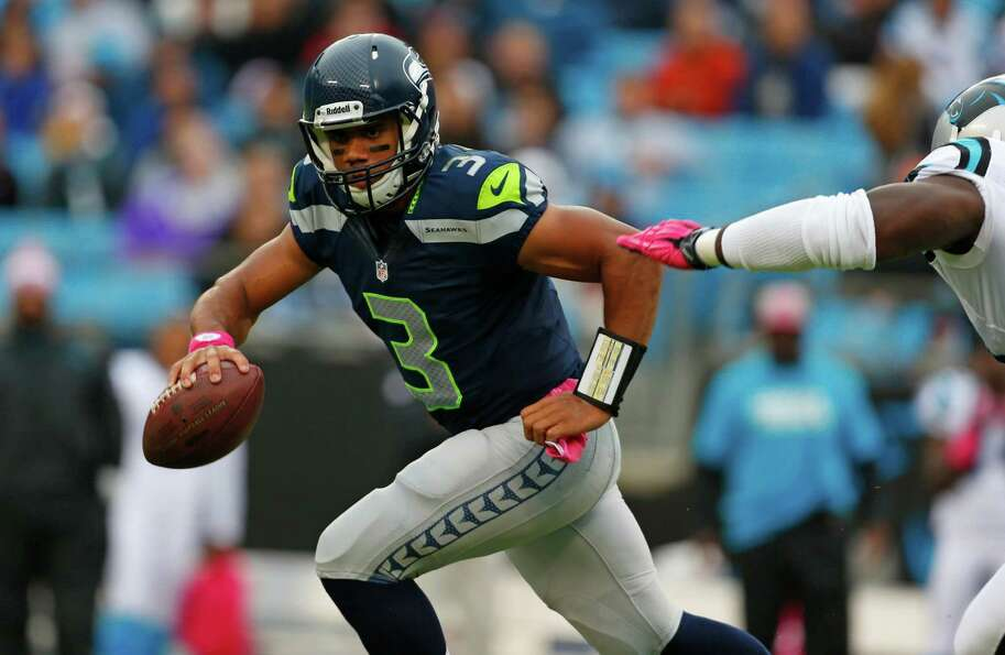Seattle Seahawks' Russell Wilson (3) scrambles under pressure from the Carolina Panthers during the