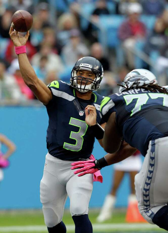 Seattle Seahawks' Russell Wilson (3) throws a pass under pressure during the first quarter of an NFL football game against the Carolina Panthers in Charlotte, N.C., Sunday, Oct. 7, 2012. Photo: AP