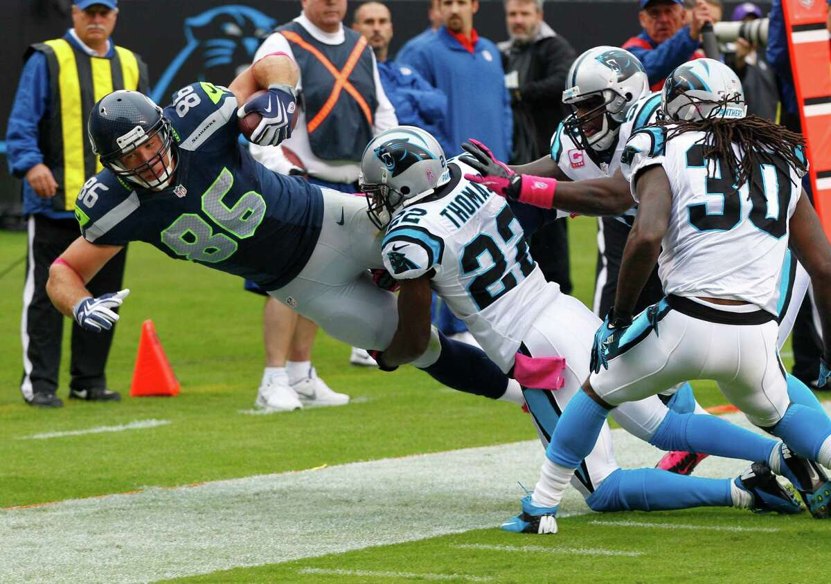 Seattle Seahawks' Anthony McCoy (85) is knocked out of bounds by Carolina Panthers' Josh Thomas (22), Charles Godfrey (30), and Thomas Davis (58) during the first quarter of an NFL football game in Charlotte, N.C., Sunday, Oct. 7, 2012.