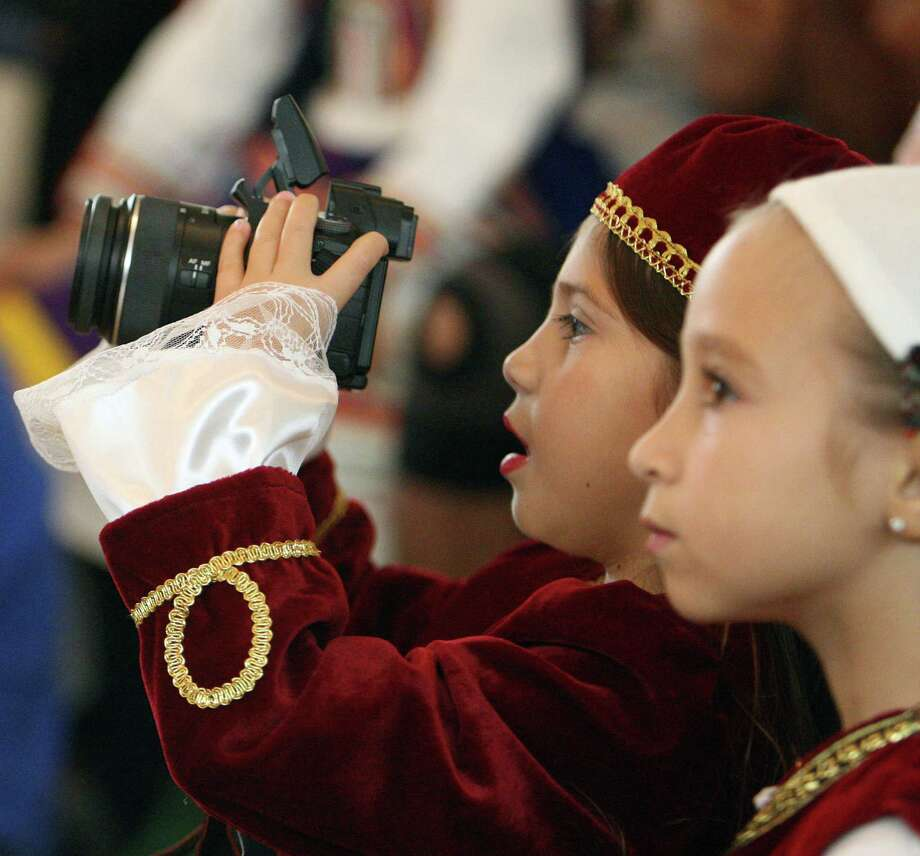 Sophia Karavantos-Schnur left, uses a camera as Sophia Stephens right, looks on during a children's dance program performance The Original Greek Festival at the Annunciation Orthodox Cathedral Sunday, Oct. 7, 2012, in Houston. Photo: James Nielsen, Chronicle / © Houston Chronicle 2012