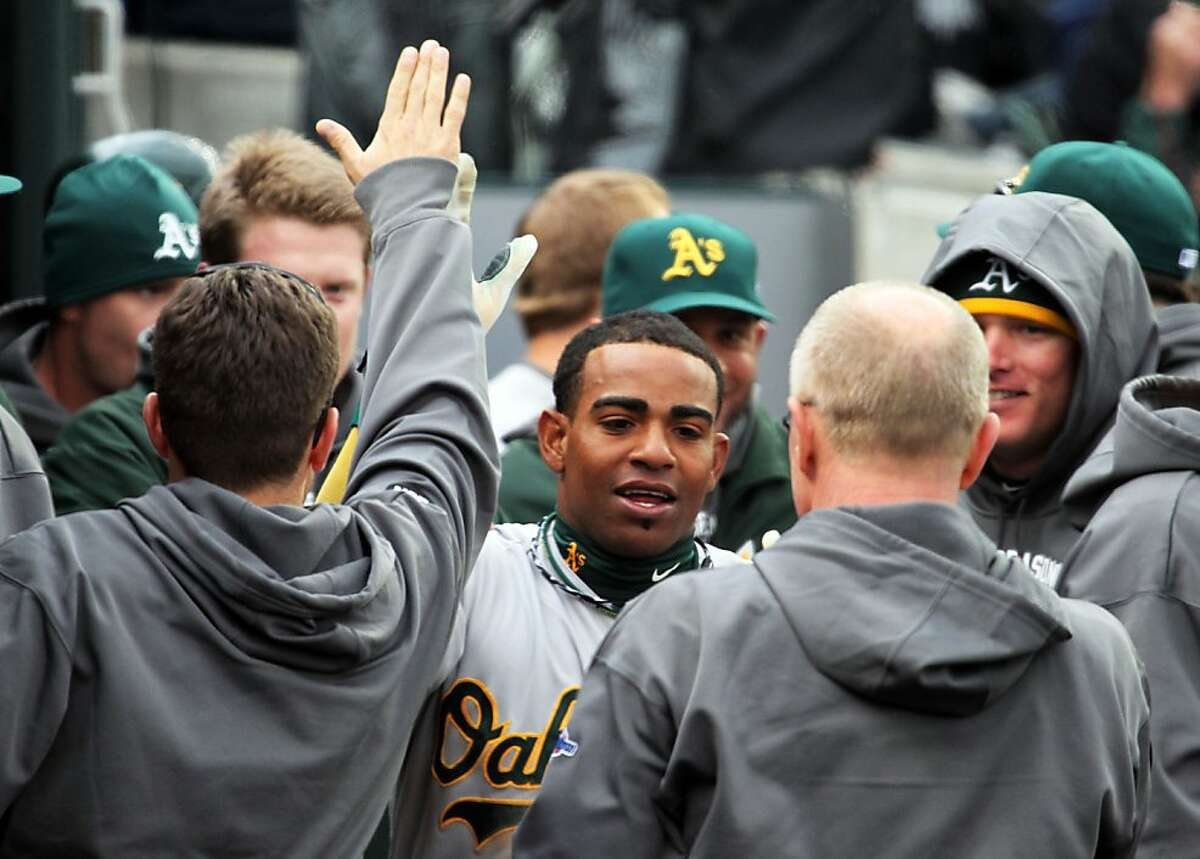 Oakland Athletics is greeted in the dugout after scoring on a passed ball in the 8th inning against the Detroit Tigers in their ALDS game Sunday October 7, 2012 in Detroit MI