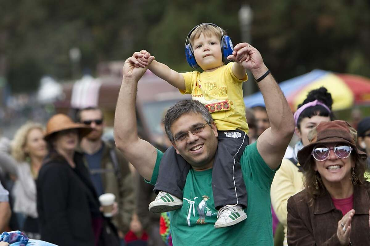 Benjamin Rifkin holds up his son while watching The New Orleans Bingo! Show perform on the porch stage at Hardly Strictly Bluegrass in Golden Gate Park in San Francisco, Calf., on Sunday, October 7, 2012.