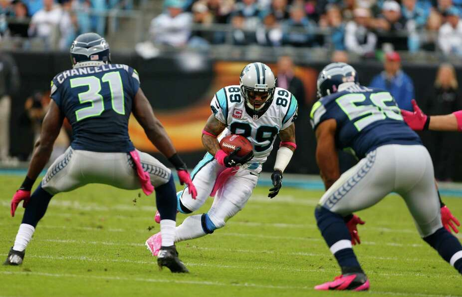 Carolina Panthers' Steve Smith (89) runs after a catch as Seattle Seahawks' Kam Chancellor (31) and