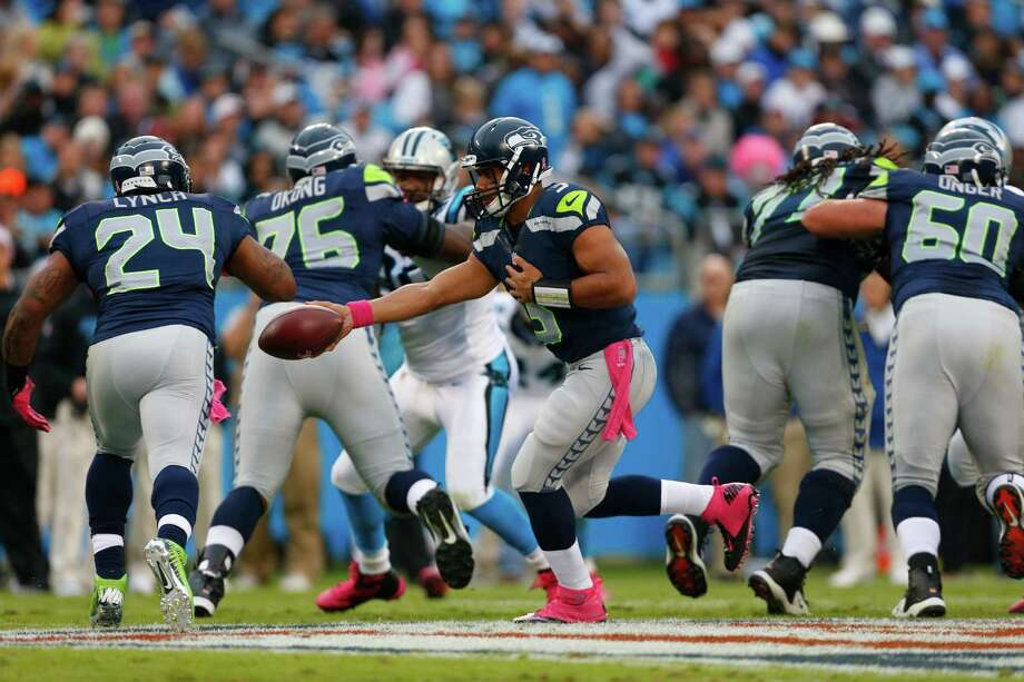 Seattle Seahawks' Russell Wilson (3) hands the ball of to Marshawn Lynch (24) during the first quarter of an NFL football game against the Carolina Panthers in Charlotte, N.C., Sunday, Oct. 7, 2012. Photo: AP