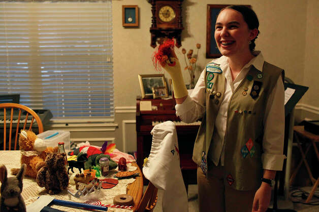 Girl Scout Rebecca Baumgarten, who is visually impaired, holds up an item that goes in one of the book bags she made for blind and visually impaired children. Photo: Lisa Krantz, San Antonio Express-News / San Antonio Express-News