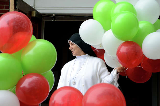 Sister Enrica Capalbo holds a bunch of balloons on the steps of Sacred Heart Church on Schuyler Avenue in Stamford during the Columbus Day Parade on Sunday, Oct. 7. Photo: Amy Mortensen / Connecticut Post Freelance