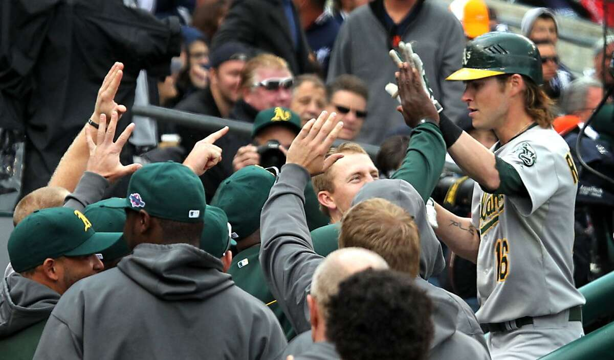 Oakland Athletics Josh Reddick is greeted in the dugout after hitting a home run in the 8th inning against the Detroit Tigers in their ALDS game Sunday October 7, 2012 in Detroit MI