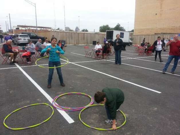Micheline, 12, and John, 7, Haralson hoola hooped to the music with their sister, Anna (not shown), during Culinaria's Feastival event at Pearl.  (Jennifer McInnis / San Antonio Express-News)