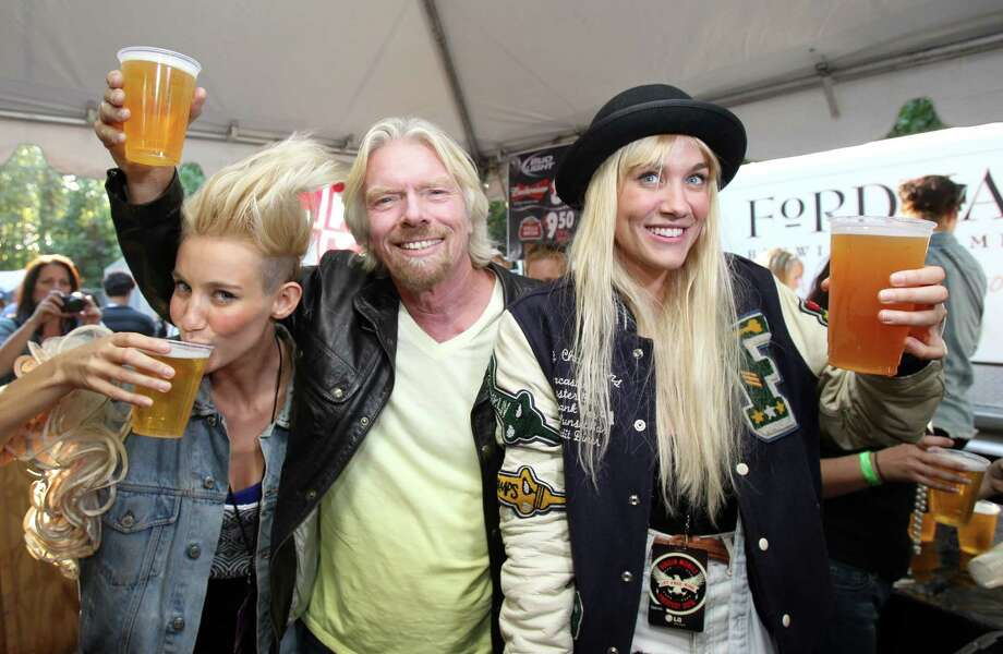 Richard Branson, chairman and founder of Virgin Group Ltd., guest bartends with Olivia Nervo (L) and Miriam Nervo of Nervo at the 2012 Virgin Mobile FreeFest on Saturday, October 6, 2012 in Columbia, Maryland. (Photo by Paul Morigi / Invision for Virgin Mobile/AP Images) Photo: Paul Morigi, Associated Press / Invision
