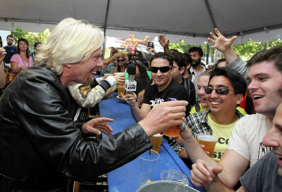 Richard Branson, chairman and founder of Virgin Group Ltd., guest bartends at the 2012 Virgin Mobile FreeFest on Saturday, October 6, 2012 in Columbia, Maryland. (Photo by Paul Morigi / Invision for Virgin Mobile/AP Images) Photo: Paul Morigi, Associated Press / Invision
