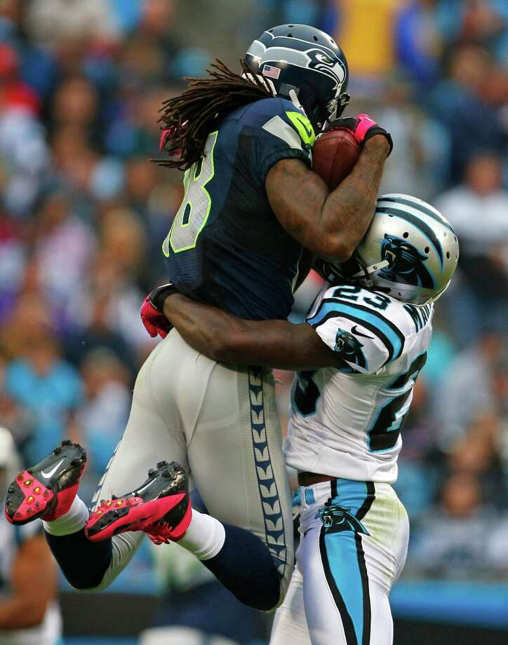 Seattle Seahawks' Sidney Rice (18) catches a pass as Carolina Panthers' Sherrod Martin (23) defends during the second quarter of an NFL football game in Charlotte, N.C., Sunday, Oct. 7, 2012. Photo: AP