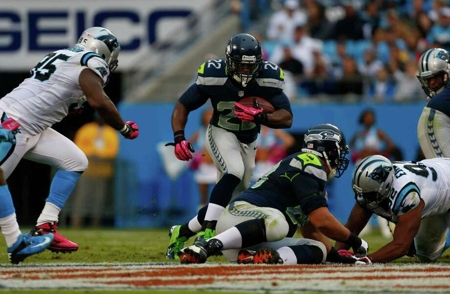 Seattle Seahawks' Marshawn Lynch (24) runs as Carolina Panthers' Charles Johnson (95) defends during the second quarter of an NFL football game in Charlotte, N.C., Sunday, Oct. 7, 2012. Photo: AP