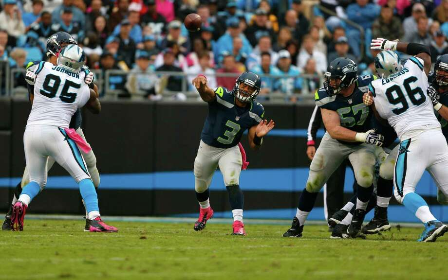 Seattle Seahawks' Russell Wilson (3) throws a pass under pressure from the Carolina Panthers during the second quarter of an NFL football game in Charlotte, N.C., Sunday, Oct. 7, 2012. Photo: AP