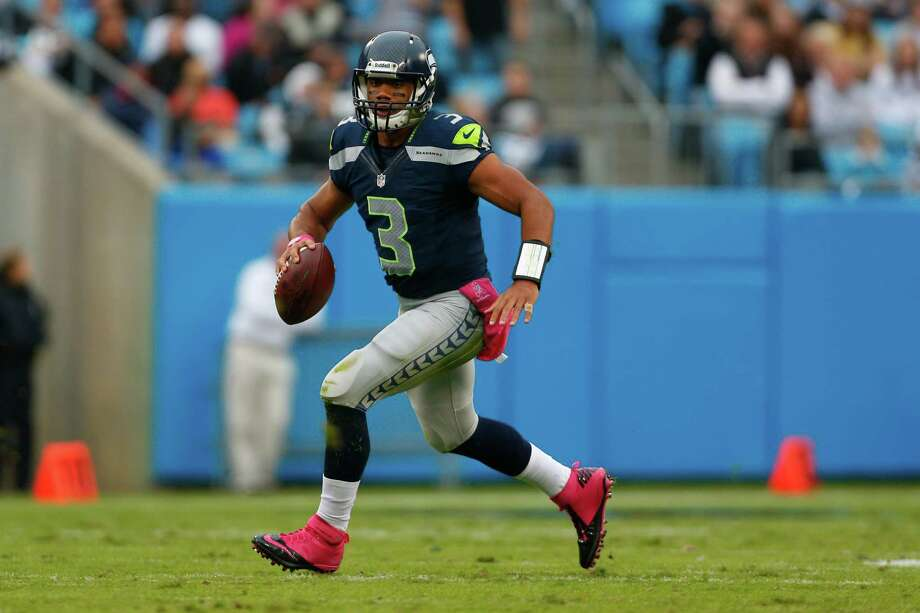 Seattle Seahawks' Russell Wilson (3) scrambles against the Carolina Panthers defend during the second quarter of an NFL football game in Charlotte, N.C., Sunday, Oct. 7, 2012. Photo: AP