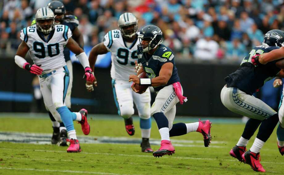 Seattle Seahawks' Russell Wilson (3) scrambles as Carolina Panthers' Frank Alexander (90), and Frank Kearse (99) defend during the second quarter of an NFL football game in Charlotte, N.C., Sunday, Oct. 7, 2012. Photo: AP