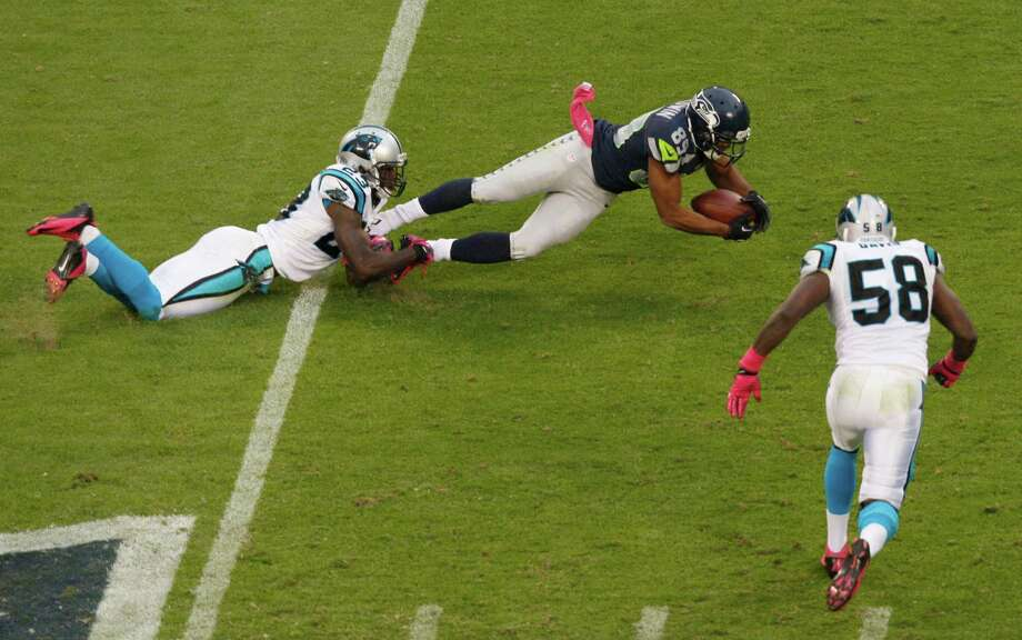 Seattle Seahawks' Doug Baldwin (89) is tackled by Carolina Panthers' Sherrod Martin (23) as Thomas Davis (58) runs in during the second quarter of an NFL football game in Charlotte, N.C., Sunday, Oct. 7, 2012. Photo: AP