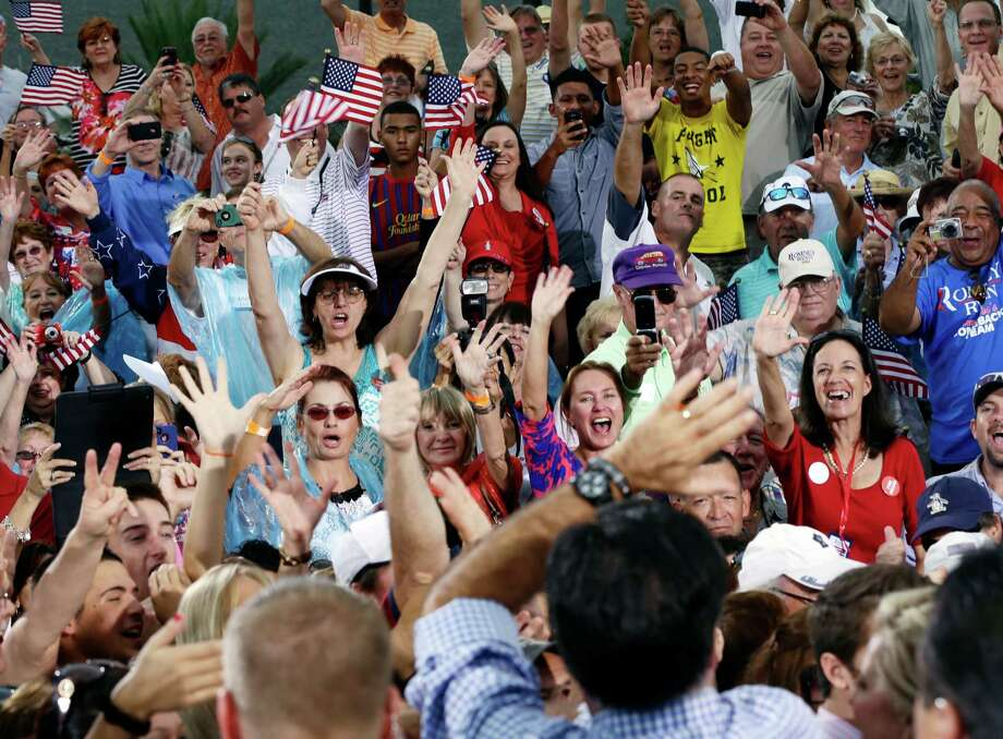 Republican presidential candidate and former Massachusetts Gov. Mitt Romney, foreground, waves to supporters as he campaigns at Tradition Town Square in Port St. Lucie, Fla. Photo: Charles Dharapak, Associated Press / AP