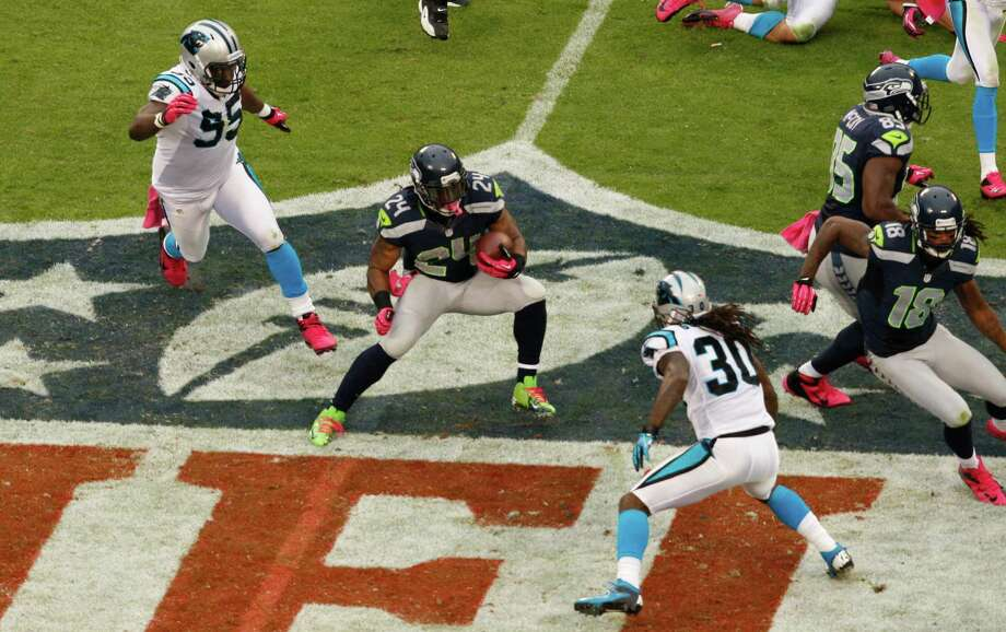 Seattle Seahawks' Marshawn Lynch (24) runs as Carolina Panthers' Charles Johnson (95) and Charles Godfrey (30) defend during the second quarter of an NFL football game in Charlotte, N.C., Sunday, Oct. 7, 2012. Photo: AP