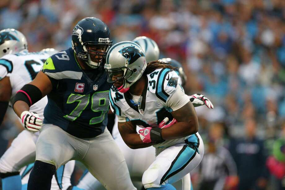 Carolina Panthers' DeAngelo Williams (34) runs as Seattle Seahawks' Red Bryant (79) defends during the second quarter of an NFL football game in Charlotte, N.C., Sunday, Oct. 7, 2012. Photo: AP