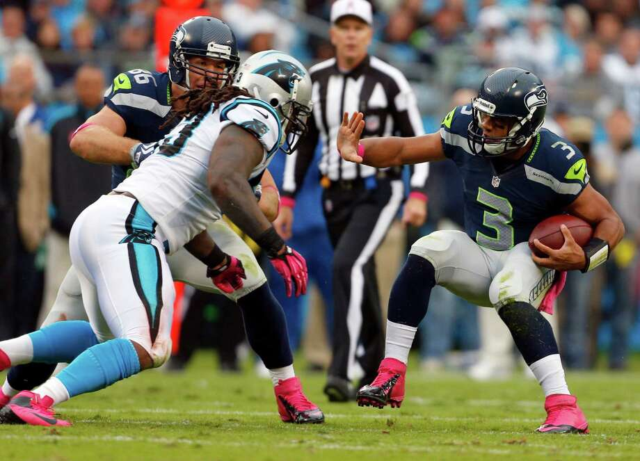 Seattle Seahawks' Russell Wilson (3) tries to scramble past Carolina Panthers' Antwan Applewhite (93) during the second quarter of an NFL football game in Charlotte, N.C., Sunday, Oct. 7, 2012. Photo: AP