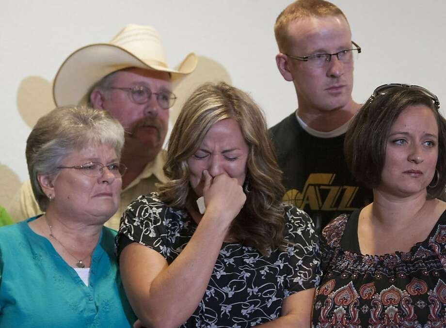 Christy Ivie (center), surrounded by family, mourns the loss of her husband, agent Nicholas Ivie. Photo: Gary M Williams, Associated Press