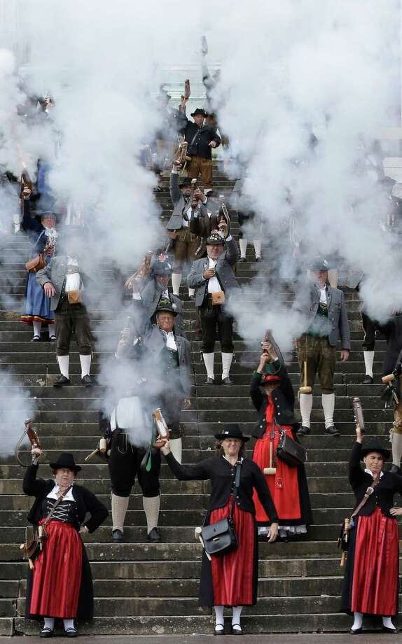 Bavarian riflemen and women in traditional costumes fire their muzzle loading guns in Munich, southern Germany, Sunday, Oct. 7, 2012. Members of various shooting clubs of the region met for a salute on the last day of the famous Oktoberfest beer festival. (AP Photo/Matthias Schrader) Photo: Matthias Schrader