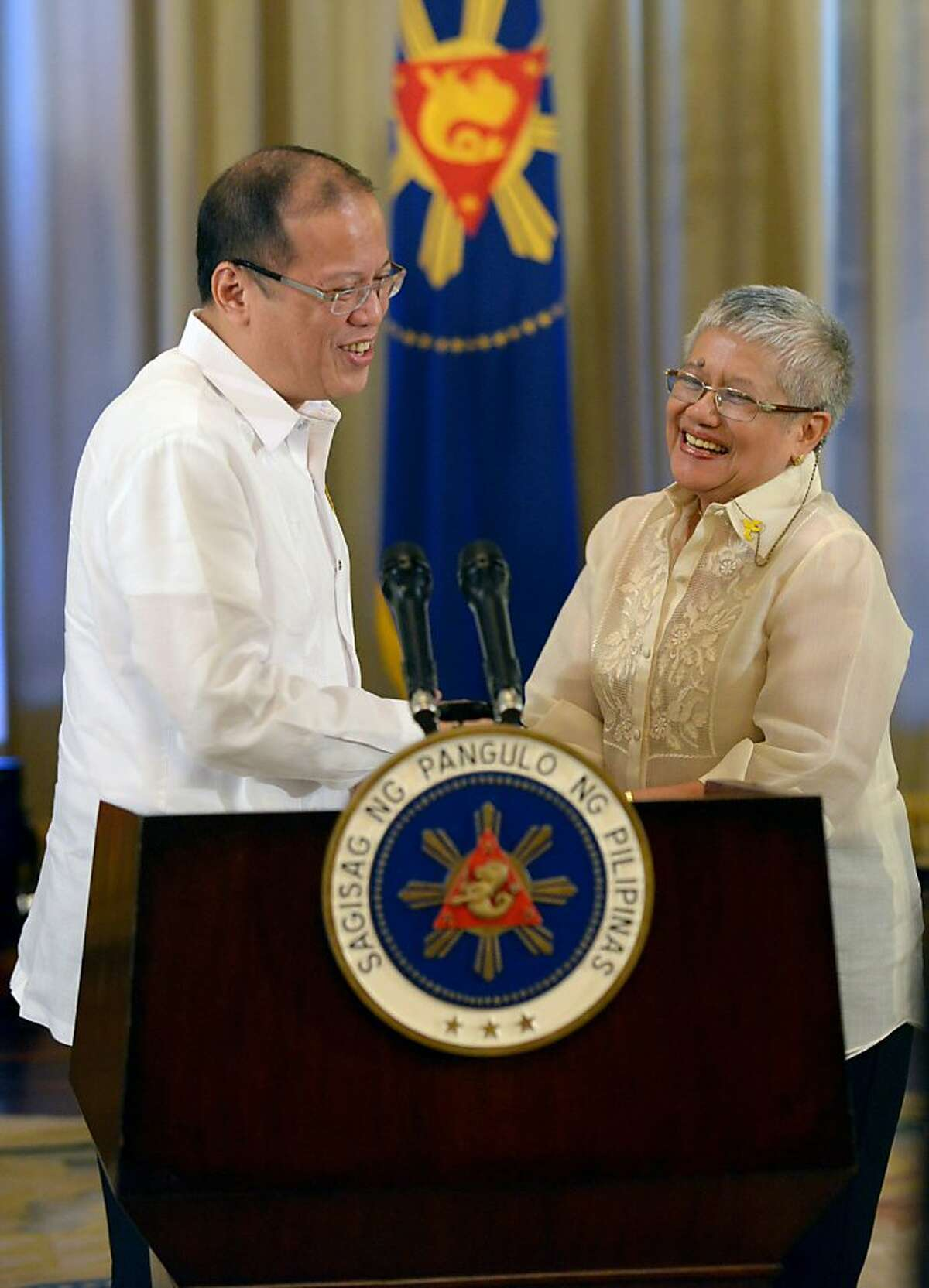 Philippines President Benigno Aquino (L) shakes hands with Presidential Adviser on the Peace Process, Secretary Teresita Quintos-Deles (R) at the Malacanang Palace in Manila on October 7, 2012. Philippine Muslim rebels said on October 7 they were