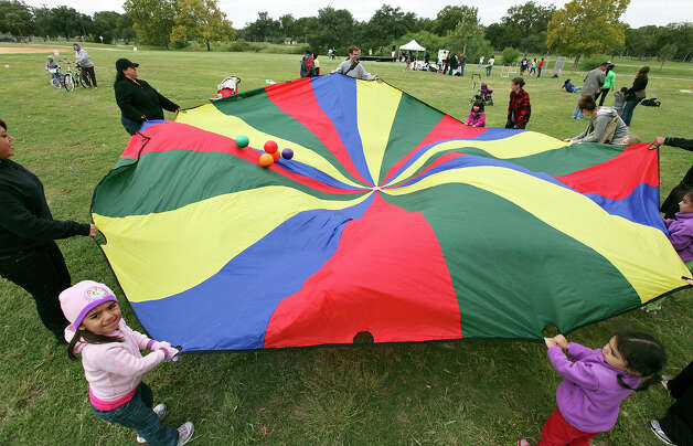 Adults and children play a parachute game at Lions Field on Sunday Oct. 7, 2012 during Siclovia. Photo: Edward A. Ornelas, San Antonio Express-News / © 2012 San Antonio Express-News