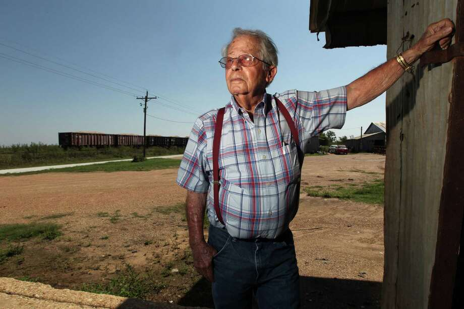 A Union Pacific train passes behind Gathan Reistino, 85, on his farmland near where the railroad wants to build a massive switching yard. It has threatened to seize through eminent domain the land Reistino refuses to sell. Photo: James Nielsen / © Houston Chronicle 2012