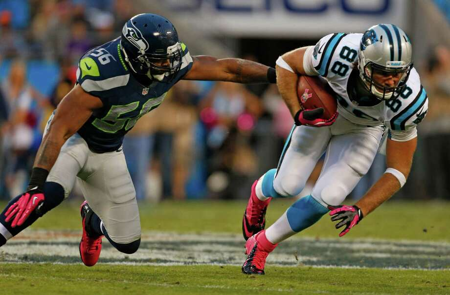 Carolina Panthers' Greg Olsen (88) runs after a catch as Seattle Seahawks' Leroy Hill (56) defends during the fourth quarter of an NFL football game in Charlotte, N.C., Sunday, Oct. 7, 2012. The Seahawks won 16-12. Photo: AP
