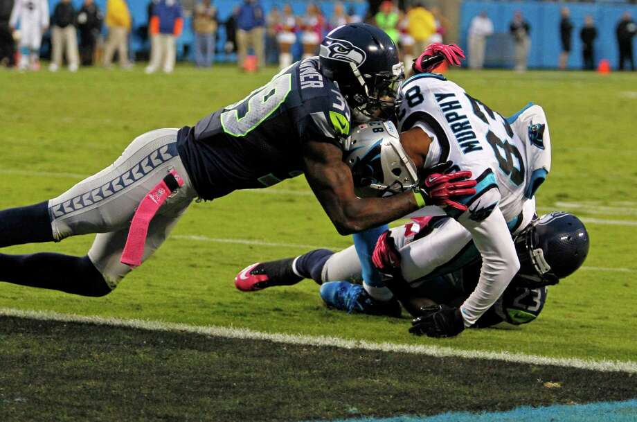 Carolina Panthers' Louis Murphy (83) is stopped short of the end zone by Seattle Seahawks' Brandon Browner (39) and  Marcus Trufant (23) during the fourth quarter of an NFL football game in Charlotte, N.C., Sunday, Oct. 7, 2012. The Seahawks won 16-12. Photo: AP