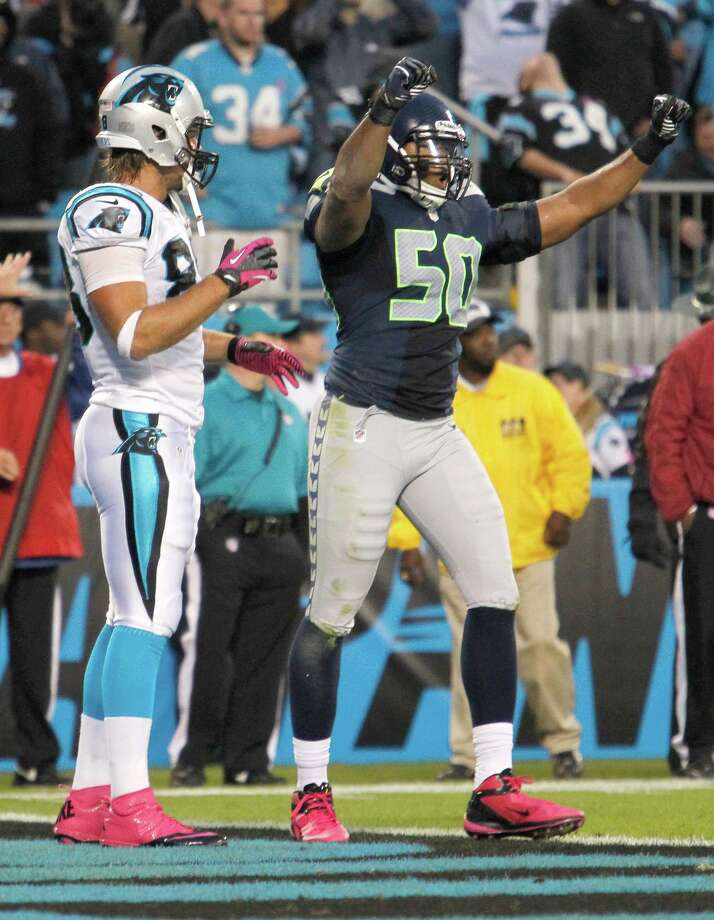 Seattle Seahawks' K.J. Wright (50) reacts as Carolina Panthers' Greg Olsen (88) stands by after the Panthers' incomplete pass on fourth down during the fourth quarter of an NFL football game in Charlotte, N.C., Sunday, Oct. 7, 2012. The Seahawks won 16-12. Photo: AP