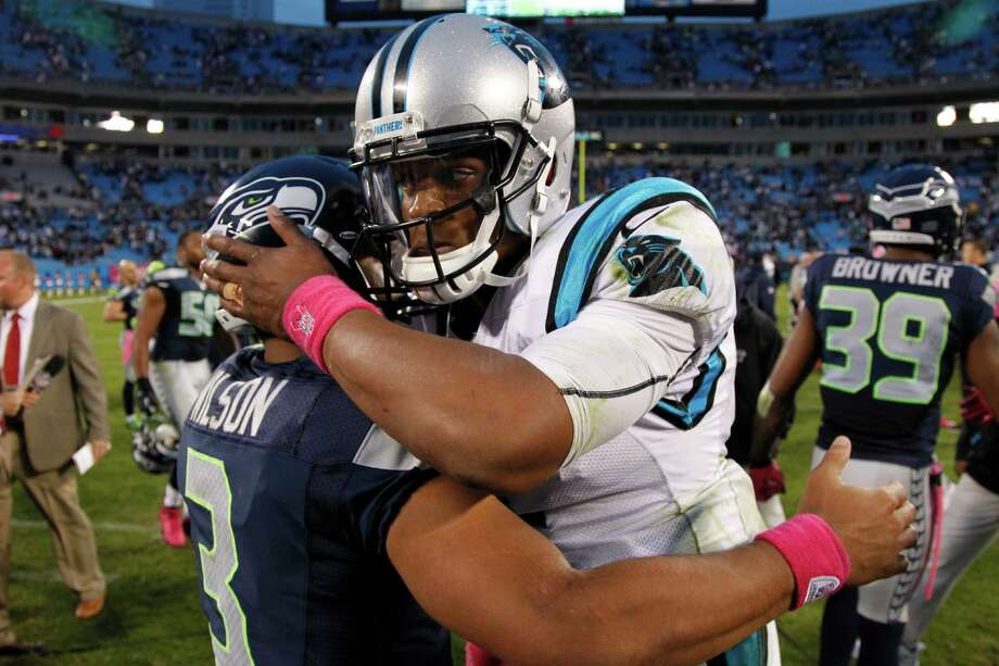 Carolina Panthers' Cam Newton, right, embraces Seattle Seahawks' Russell Wilson, left, after an NFL football game in Charlotte, N.C., Sunday, Oct. 7, 2012. The Seahawks won 16-12. Photo: AP