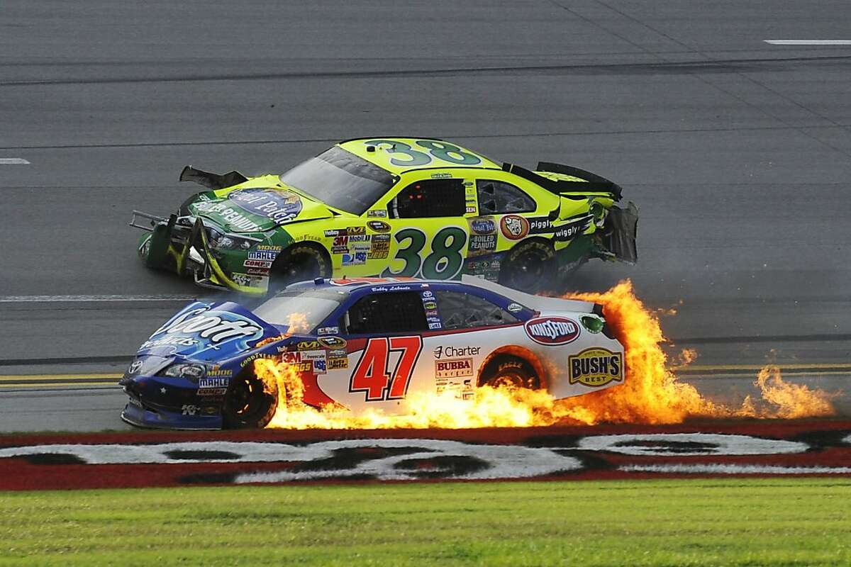 Flames engulf Bobby Labonte's car as David Gilliland (38) passes after wrecking on the last lap of the NASCAR Sprint Cup Series auto race at Talladega Superspeedway in Talladega, Ala., Sunday, Oct. 7, 2012. (AP Photo/Rainier Ehrhardt)