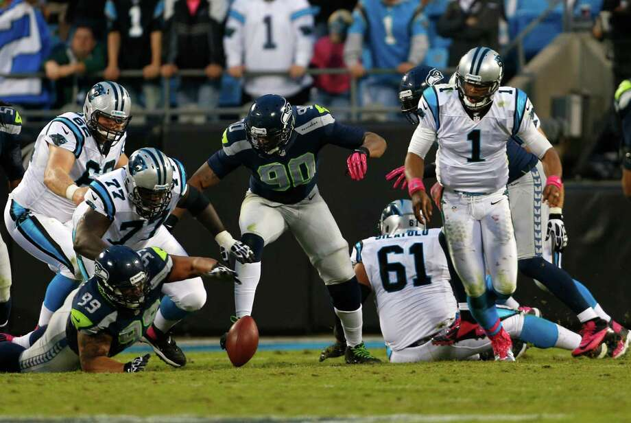 Seattle Seahawks' Alan Branch (99) reaches for the ball after Carolina Panthers' Cam Newton (1) fumbles during the fourth quarter of an NFL football game in Charlotte, N.C., Sunday, Oct. 7, 2012. The Seahawks recovered the ball and won 16-12. Photo: AP
