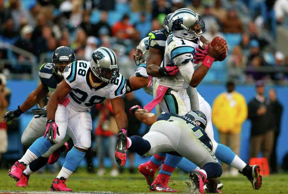 Carolina Panthers' Cam Newton (1) is tackled by Seattle Seahawks' Chris Clemons (91) and  Bobby Wagner (54) during the third quarter of an NFL football game in Charlotte, N.C., Sunday, Oct. 7, 2012. Photo: AP
