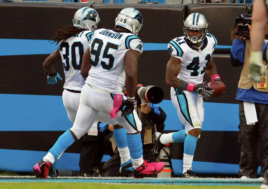 Carolina Panthers' Captain Munnerlyn (41) celebrates his interception return for a touchdown with teammates  Charles Johnson (95) and  Charles Godfrey (30)during the third quarter of an NFL football game against the Seattle Seahawks in Charlotte, N.C., Sunday, Oct. 7, 2012. Photo: AP