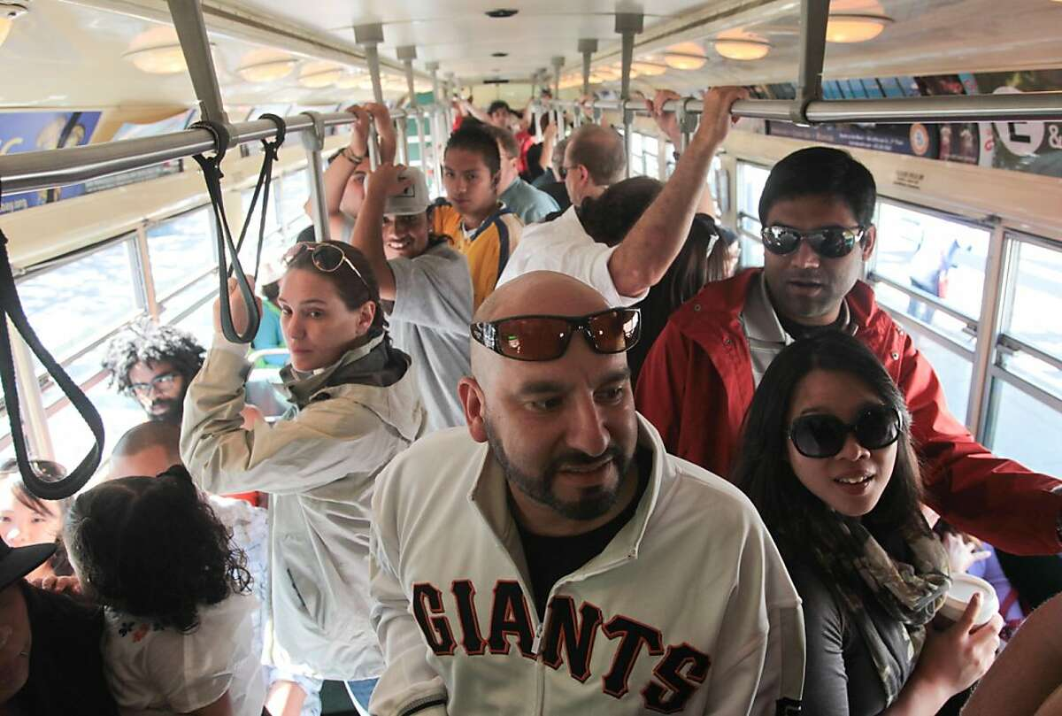 Edward Tovar of Chowchilla (Madera County) prepares to exit a packed F-Market streetcar! to watch the S.F. Giants play the Cincinnati Reds at AT&T Park, where the Reds won 9-0.