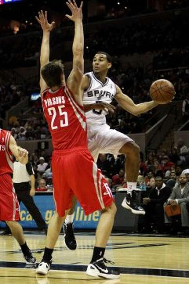 SPURS -- San Antonio Spurs guard Cory Joseph passes around Houston Rockets forward Chandler Parsons during the second half of an NBA preseason game at the AT&T Center in San Antonio, Wednesday, Dec. 21, 2011. The Spurs won 97-95. JERRY LARA/glara@express-news.net (San Antonio Express-News)
