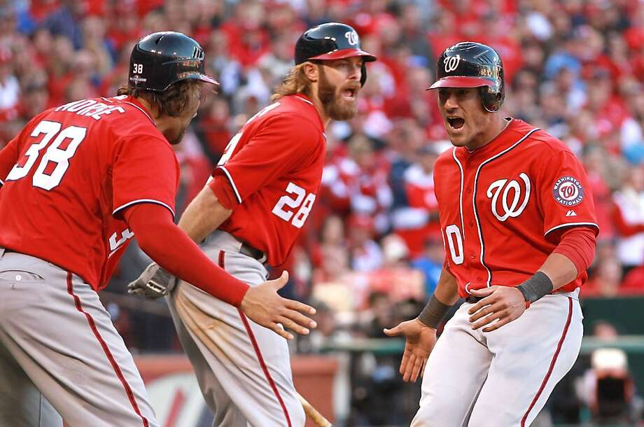 Tyler Moore's single brought in Michael Morse (left) and Ian Desmond (right) with the tying and go-ahead runs. They were greeted by Jayson Werth. Photo: Dilip Vishwanat, Getty Images