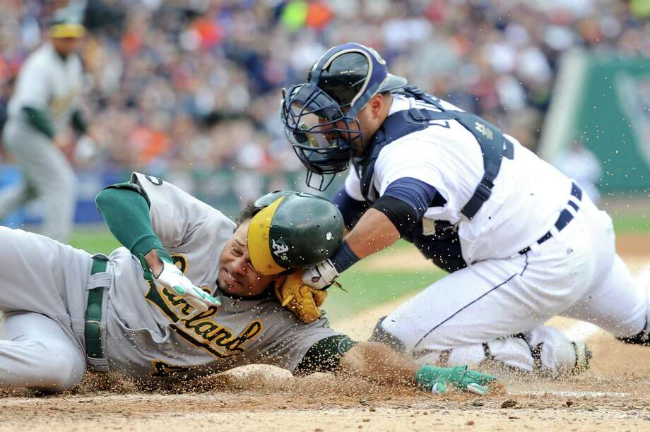 The Tigers' Gerald Laird applies the tag to cut down the Athletics' Coco Crisp in the third inning. Photo: Jason Miller / 2012 Getty Images
