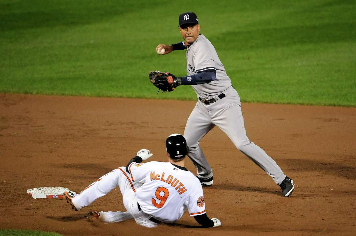 BALTIMORE, MD - OCTOBER 07: Derek Jeter #2 of the New York Yankees forces out Nate McLouth #9 of the Baltimore Orioles as he turns a double play on a ball hit by J.J. Hardy #2 of the Orioles during Game One of the American League Division Series at Oriole Park at Camden Yards on October 7, 2012 in Baltimore, Maryland. (Photo by Patrick McDermott/Getty Images)